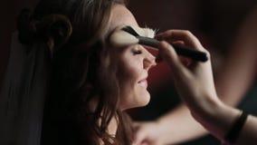 Den yrkesmässiga makeupkonstnären förbereder huden av en ung härlig brud i ett bröllop lager videofilmer