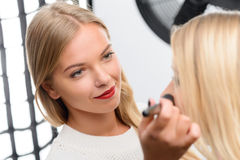 Den yrkesmässiga makeupkonstnären tycker om hennes arbete arkivbilder
