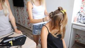 Den yrkesmässiga manliga barberaren lägger hår av den blonda flickan vid hårkammen och hårtorken i skönhetsalong spegel Danandevo arkivfilmer