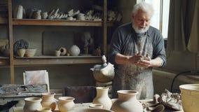 Den yrkesmässiga manliga ceramisten knådar lera som bildar lerabollen, medan arbeta i litet seminarium med utrustning för keramik stock video
