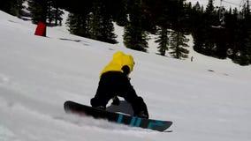 Den yrkesmässiga manliga snowboarderen hoppar på snowboarden som utför jippon på extremt landskap för kulle för berg för sportrut arkivfilmer