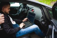 Den yrkesmässiga mannen med en bärbar dator i bil trimmar att trimma kontrollsystemet och att uppdatera programvara som igenom få Arkivfoton