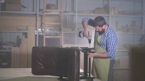 Den yrkesmässiga mannen med ett skägg i en skjorta kopplas in, i att förse med underlag montera en möblemangstol i ett mörkt semi stock video