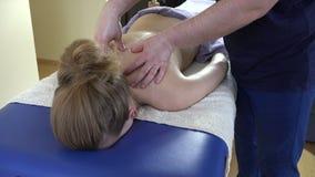 Den yrkesmässiga massörmannen gör att koppla av tillbaka massagekvinnan arkivfilmer