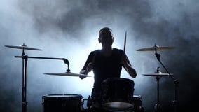 Den yrkesmässiga musikern spelar musik på valsar med hjälpen av pinnar rökig bakgrund silhouette lager videofilmer