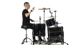 Den yrkesmässiga musikern spelar musik på valsar med hjälpen av pinnar Vit bakgrund Slapp fokus stock video