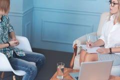 Den yrkesmässiga psykoterapeuten diskuterar ångest och oroar med den tonåriga pojken arkivfoto