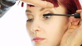 Den yrkesmässiga sminkkonstnären färgar ögonen av modellen stylisten målar ögonfrans