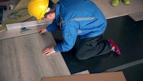Den yrkesmässiga snickaremannen lägger trälaminaten på golv stock video
