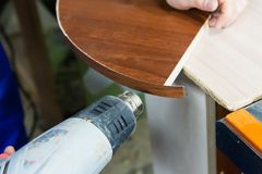 Den yrkesmässiga snickaren på arbete torkar ett träd vid en yrkesmässig industriell närbild för handtool för hårtork av ett snick arkivbild