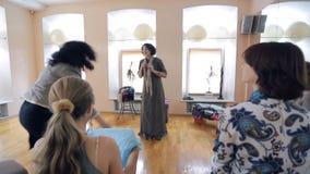 Den yrkesmässiga stylisten utbildar fashionistas i vägar att binda en halsduk stock video