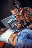 Den yrkesm?ssiga tattooisten drar en tatuering royaltyfri fotografi
