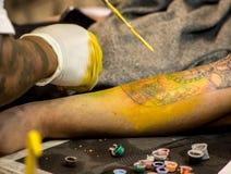 Den yrkesmässiga tatueringkonstnären gör en tatuering royaltyfria bilder