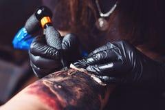 Den yrkesmässiga tatueringkonstnären gör en tatuering på en hand för man` s fotografering för bildbyråer