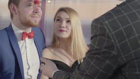 Den yrkesmässiga trollkarlen visar ett trick till ett härligt par Grabben och flickan är förvånade och jätteglade med magin arkivfilmer