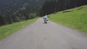 Den yrkesmässiga unga skateboarderen utför jippon som rider för landssidan för longboarden den sluttande vägen i fantastiskt skog arkivfilmer