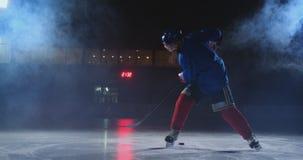 Den yrkesm?ssiga hockeyspelaren med en pinne och en puck flyttar sig p? Luda i skridskor och hj?lm p? en m?rk bakgrund och r?k stock video