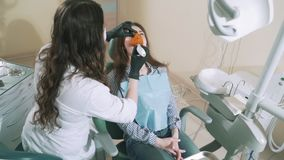 Den Zahnarzt in ihrem Büro langsam schießen legte eine Dichtung auf das junge Mädchen dem Patienten vor und wärmt sie mit a stock footage
