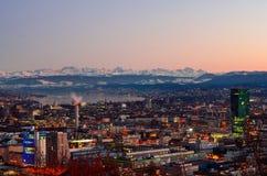 Den Zurich staden förbiser på solnedgången arkivfoto