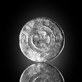 Denar cross-Saxon Old silver coin exposed on black reflecting glass, found in life dig by metal detector.England. Stock Photos
