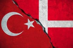 Denemarken de rode Turkije vlag versus van Turkije, op gebroken schadebakstenen muur en halve de vlagachtergrond van Denemarken,  royalty-vrije stock afbeelding