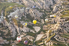denfärgade luftshataflugan över vaggar i Cappadocia Arkivbild