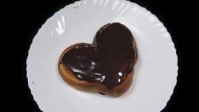 Denformade bullechokladen täckte och ligger på en vit platta och roterar på en svart bakgrund