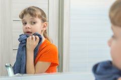 dengamla flickan torkar hennes framsida med handduken, når han har tvättat sig arkivfoton