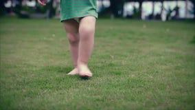 dengamla litet barnpysen går på sommaren av på det gröna gräset långsam rörelse Clouse upp lager videofilmer