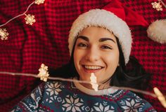 denhaired härliga unga kvinnan i en julhatt ligger på en röd pläd och rymmer en julgirland i henne händer Royaltyfria Bilder