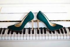 denheeled brudens skor är på pianotangenterna som är svartvita, kvinnors gröna sammetskor arkivbild