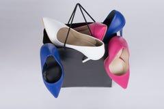 denheeled stiletten sko-fyllde shoppingpåsen och överlopp på isolerad bakgrund royaltyfria foton