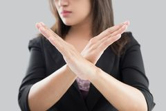 Denial. Business woman in black suit showing her denial with no on her hand against gray background Stock Photography