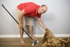 Denial is Hiding the Trash Under Rug. A concept about denial and truth, a man sweeping rubbish under a carpet stock photography