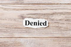 Denied of the word on paper. concept. Words of Denied on a wooden background stock photo