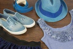 Denim blauwe schoenen, riem, T-shirt en hoed op de bruine vloer Stock Foto's
