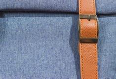 Denim blue with a brown strap . Fabrics, denim blue with a brown strap royalty free stock image