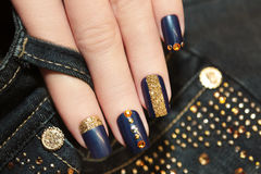 Denim blue manicure. Denim blue manicure with rhinestones and sequins stock images