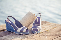 Denim blue sandals lie on wooden clutch at the lake Royalty Free Stock Photography