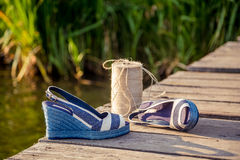 Denim blue sandals lie on wooden clutch at the lake. A Stock Photo