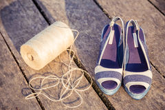 Denim blue sandals lie on wooden clutch at the lake. A Stock Photography