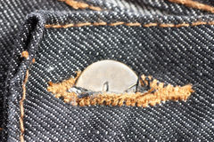 Denim button. Closeup view of half clasped button on a jeans Stock Photo