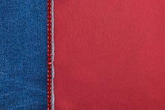 Denim décoré des fausses pierres rouges se trouvant sur le satin Photographie stock