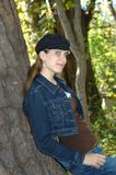 Denim Day at the Park. Young teen leans back against a tree trunk.  She has on a cap and a denim jacket and jeans Stock Photo