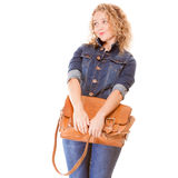 Denim fashion. College student girl in blue jeans holds bag Royalty Free Stock Image