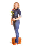 Denim fashion. Full length student girl in blue jeans bag holds red rose Royalty Free Stock Photo