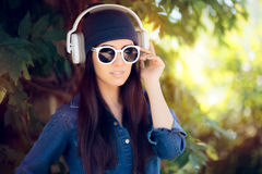 Denim Fashion Girl with Sunglasses Listening to Music on her Headphones Stock Images