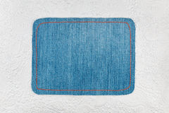 Denim frame lies on a wite leather Royalty Free Stock Photography