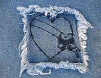 Denim Heart 2. A denim square patch containing a heart with a blank banner Stock Image