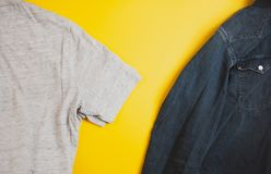 Denim jacket and grey tshirt on two sides of the photo, on yellow background, with copyspace royalty free stock images